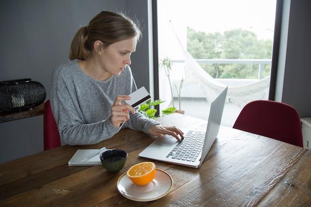Mujer joven que hace compras en línea con la tarjeta de crédito en la pc