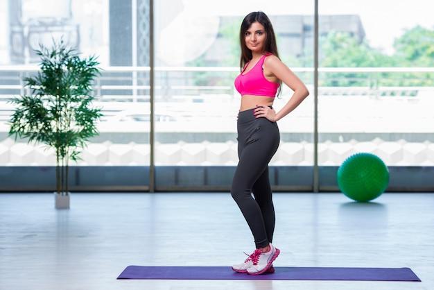 Mujer joven que hace ejercicios en concepto de la salud del gimnasio