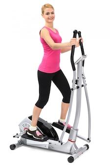 Mujer joven que hace ejercicios en el entrenador elíptico