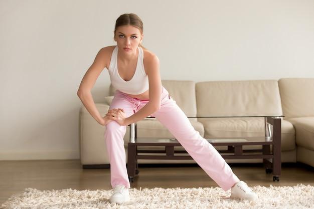 Mujer joven que hace ejercicios simples de la mañana en casa