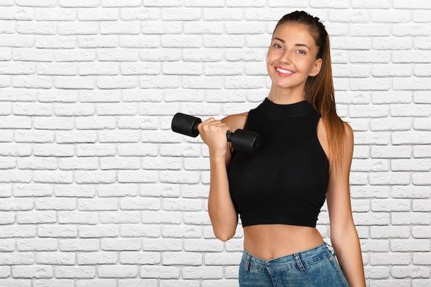 Mujer joven que hace un entrenamiento de la aptitud con pesas de gimnasia