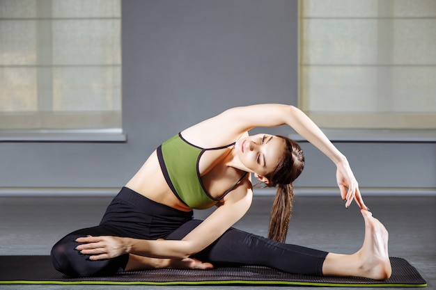 Mujer joven que hace estirando ejercicios en el estudio. yoga