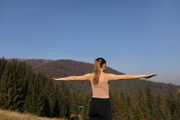 Mujer joven que hace estirando ejercicios en la naturaleza en montañas. chica deportiva practicando yoga pose en polainas. hermoso paisaje forestal