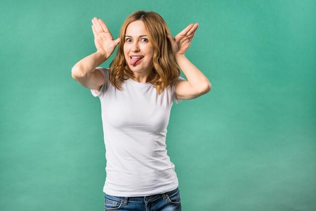 Mujer joven que hace el gesto divertido que se opone a fondo verde