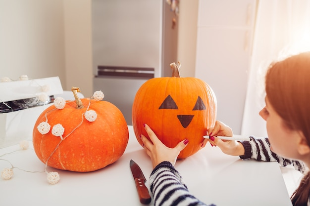Mujer joven que hace la jack-o-linterna para halloween en cocina. dibujando ojos, nariz y boca con bolígrafo sobre calabaza