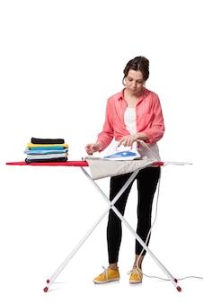 Mujer joven que hace planchar aislado en blanco
