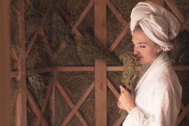 Mujer joven que huele las flores de la hierba que se colocan en la sauna
