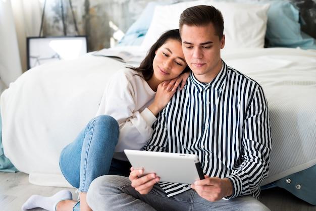 Mujer joven que se inclina en novio y que mira en la tableta