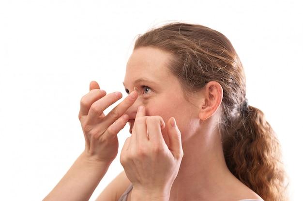 Mujer joven que inserta una lente de contacto