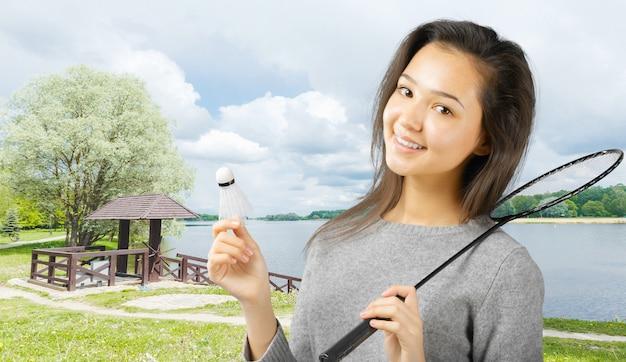 Mujer joven que juega a bádminton en un parque de la ciudad