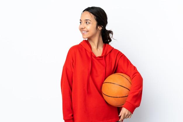 Mujer joven que juega a baloncesto sobre blanco aislado