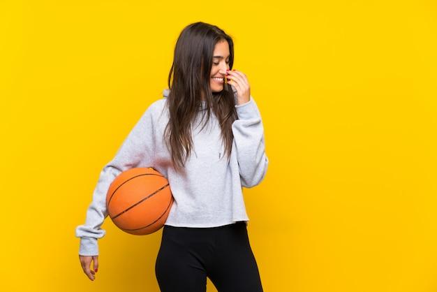 Mujer joven que juega a baloncesto sobre la pared amarilla aislada que sonríe mucho