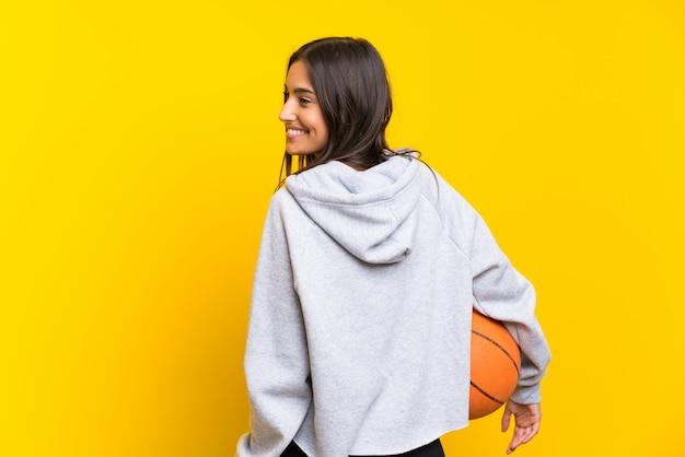 Mujer joven que juega a baloncesto sobre la pared amarilla aislada