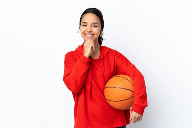 Mujer joven que juega a baloncesto sobre el pensamiento blanco