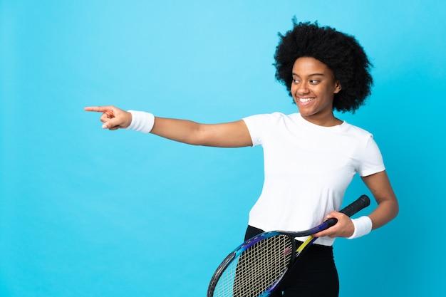 Mujer joven que juega a tenis sobre fondo aislado
