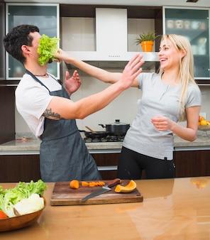 Mujer joven que juega con la verdura de la lechuga que se coloca detrás de la tabla
