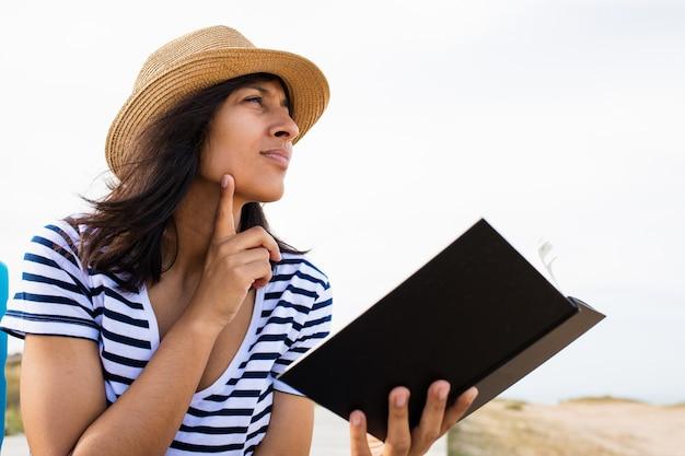 Mujer joven que lee un libro en el campo