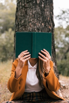 Mujer joven que lee el libro que se sienta debajo del árbol