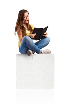 Mujer joven que lee un libro sentada en una caja blanca