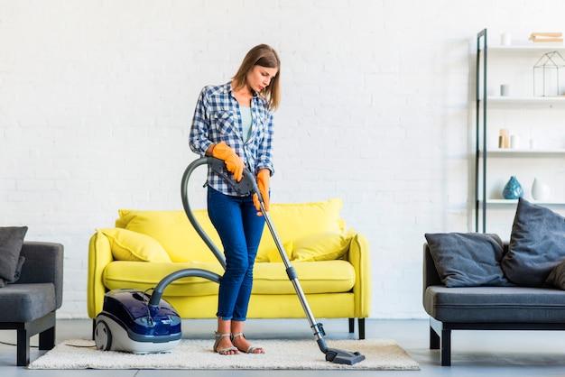 Mujer joven que limpia la alfombra con el aspirador delante del sofá amarillo