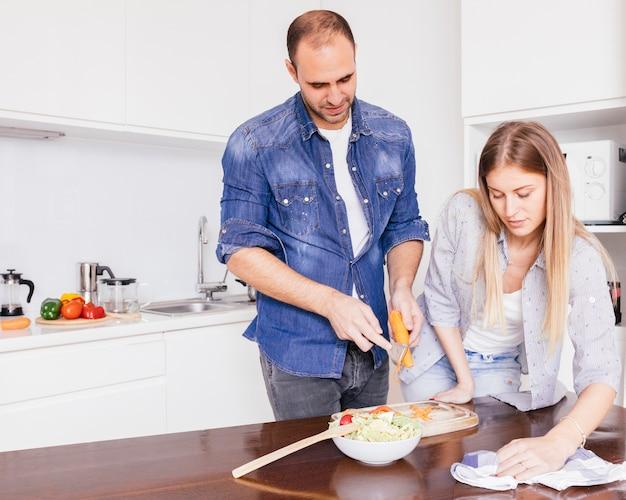 Mujer joven que limpia la mesa con la servilleta y su marido preparando la ensalada en la cocina