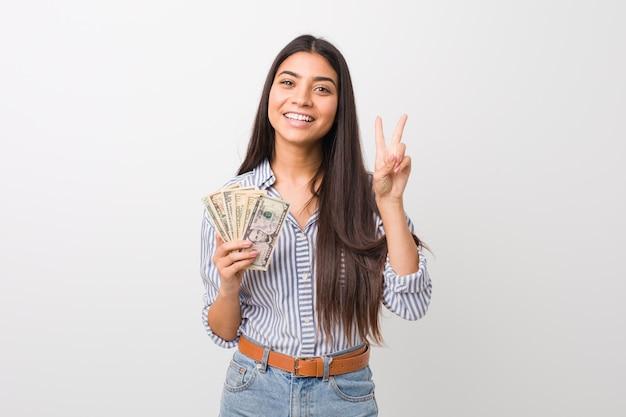Mujer joven que lleva a cabo dólares que muestran la muestra de la victoria y que sonríen ampliamente.
