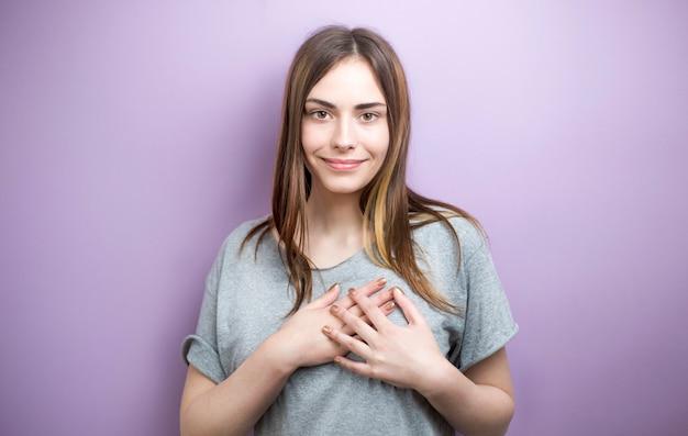 Mujer joven que lleva a cabo las manos en el pecho que siente satisfecho agradecido.