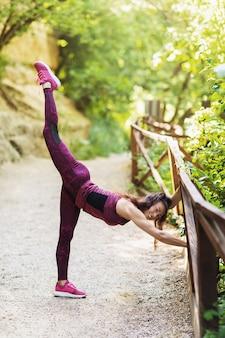 Mujer joven que lleva un estilo de vida saludable realiza ejercicios de estiramiento en una soleada mañana de verano en el parque