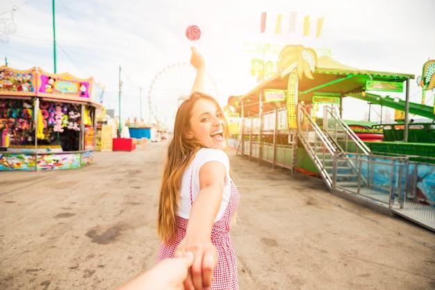 Mujer joven que lleva a su amigo que sostiene la piruleta en el parque de atracciones
