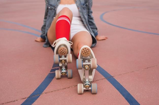 Mujer joven que llevaba patín de ruedas relajante en la corte