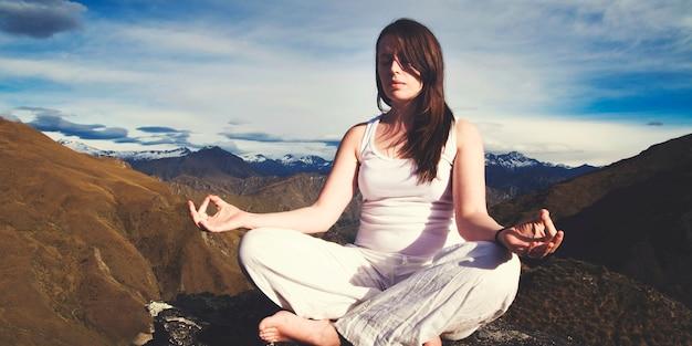 Mujer joven que medita en el desierto con la cordillera hermosa como fondo.