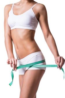 Mujer joven que mide la forma perfecta del hermoso concepto de estilos de vida saludables del muslo