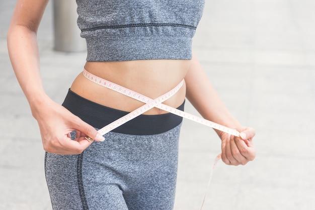 Mujer joven que mide su cintura con una cinta métrica