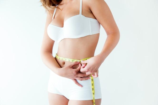 Mujer joven que mide su cintura con cinta métrica.