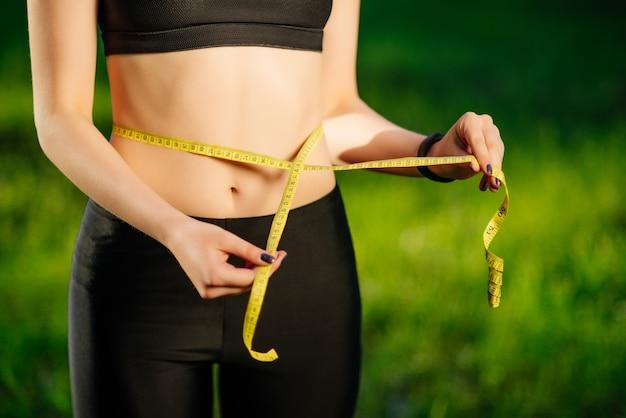 Mujer joven que mide su cintura delgada con una cinta métrica