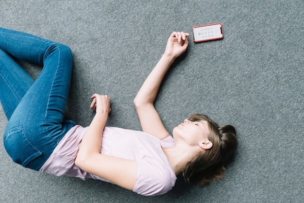 Mujer joven que miente inconscientemente en la alfombra cerca del teléfono elegante