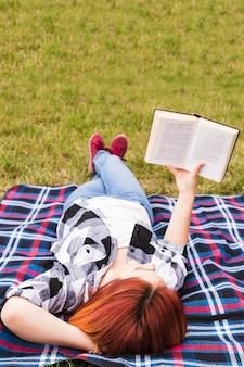 Mujer joven que miente en el libro de lectura de la manta en el parque