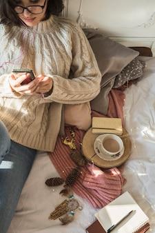 Mujer joven que miente en la manta y que usa smartphone