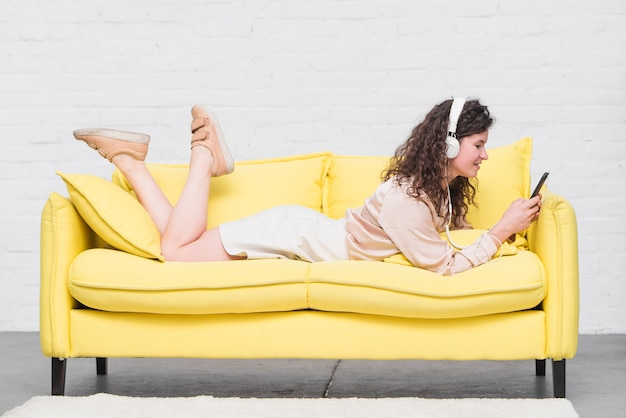 Mujer joven que miente en la música que escucha del sofá amarillo en los auriculares Foto gratis