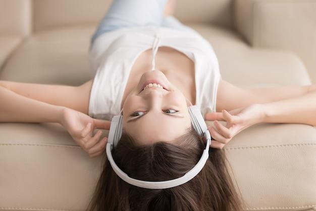 Mujer joven que miente en el sofá con los auriculares en la cabeza
