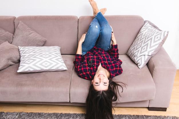 Mujer joven que miente en el sofá con sus piernas para arriba en casa