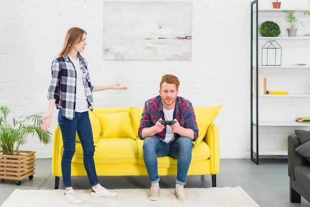 Mujer joven que mira al hombre que juega al videojuego con la palanca de mando en la sala de estar