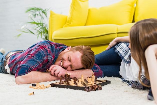 Mujer joven que mira al hombre sonriente que miente en la alfombra blanca que juega al ajedrez