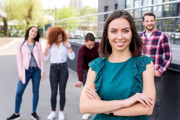 Mujer joven que mira la cámara con sus amigos en fondo borroso