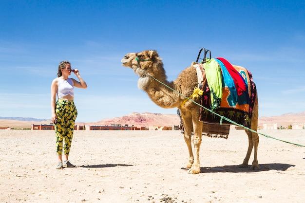Mujer joven que mira un camello en el desierto