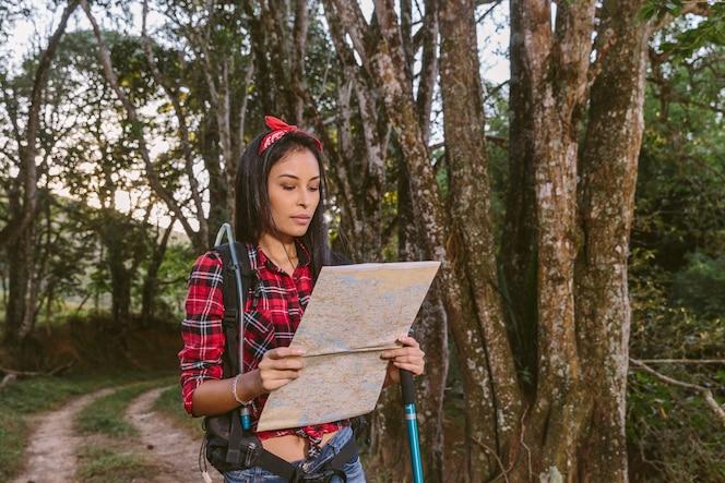 Mujer joven que mira el mapa mientras que camina en bosque