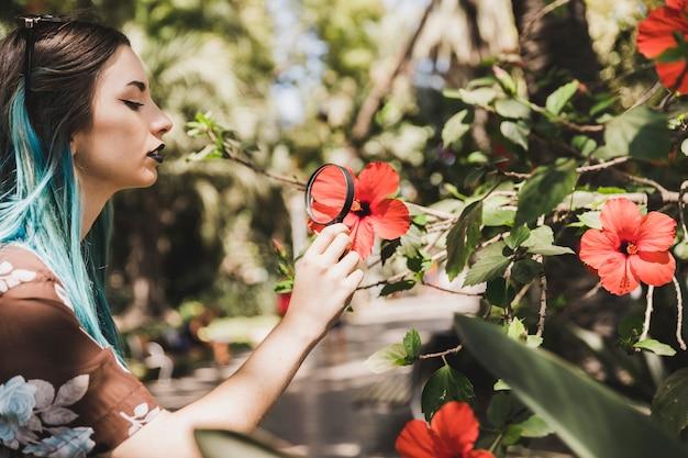 Mujer joven que mira la flor del hibisco a través de la lupa