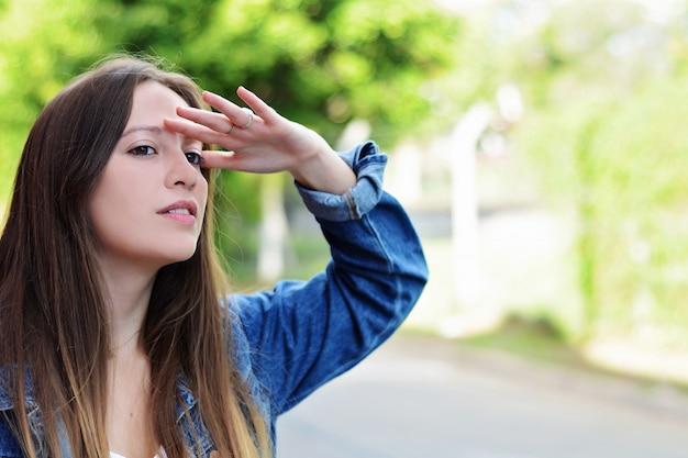 Mujer joven que mira lejos con la mano en su frente.