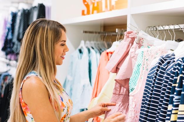 Mujer joven que mira la ropa en el estante en la sala de exposición