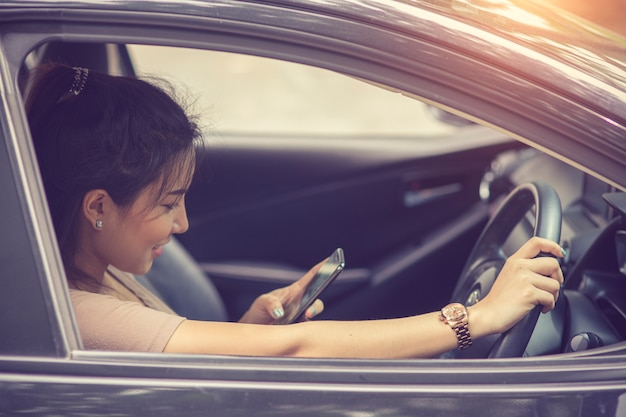 Mujer joven que mira su teléfono inteligente mientras conduce un auto en un día soleado con luz solar